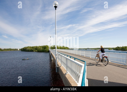 Woman cyclist on a bridge crossing River Oulujoki from Hietasaari islet to Korkiasaari islet and canoe at the river - Stock Photo