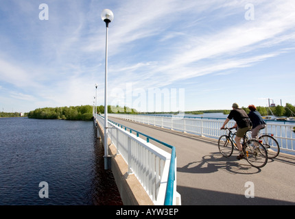 Bikers on a bridge crossing River Oulujoki from Hietasaari islet to Korkiasaari islet Oulu , Finland - Stock Photo
