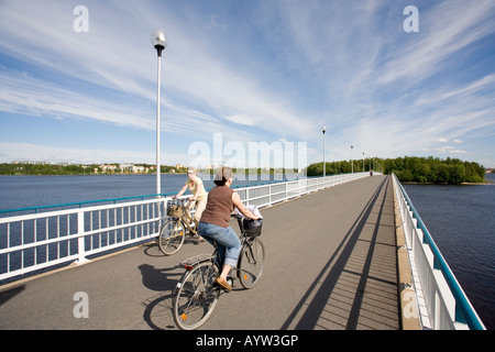 Woman cyclists on a bridge crossing River Oulujoki from Hietasaari islet to Korkiasaari islet Oulu , Finland - Stock Photo