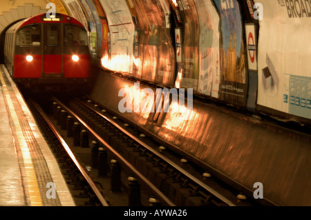 A tube train arriving on the Piccadilly Line in London UK - Stock Photo