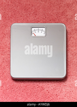 A Bathroom weighing scales on a pink fluffy carpet - Stock Photo
