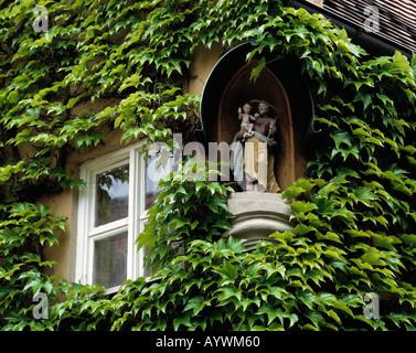 Hauswand mit Efeubewuchs, Fenster und Hauserker mit Heiligenfiguren, soziale Wohnsiedlung Fuggerei in Augsburg, - Stock Photo