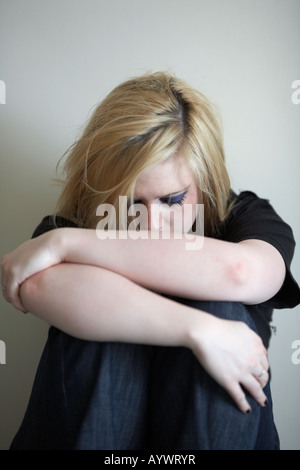 close up of arms and shoulders of blonde haired teenage woman sitting on floor with back to the wall - Stock Photo