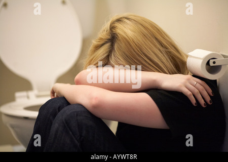 close up of arms and shoulders of blonde haired teenage woman sitting in fetal position on floor of toilet model - Stock Photo