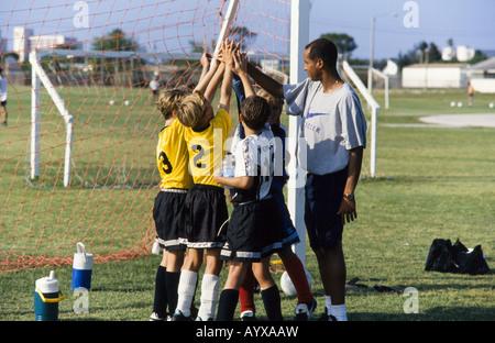 Kids soccer team, girls and boys together, with coach teaching skills, teamwork, teamspirit, Melbourne, Florida - Stock Photo