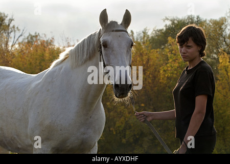The girl walks about the horse in an autumn wood - Stock Photo