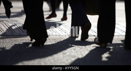 Silhouetted business people walking to work in Leeds, West Yorkshire. - Stock Photo