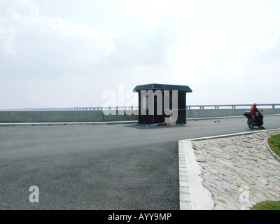 A man on a motorbike in front of Donghai Bridge Lingang New City near Shanghai China - Stock Photo