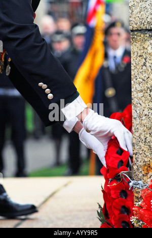 Unidentified serviceman placing placing poppy wreath on cenotaph during Remembrance day service - Stock Photo
