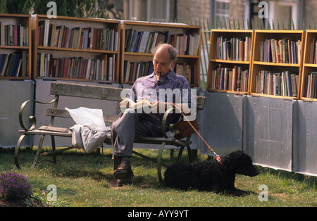 A man smoking a pipe sits on a bench in the sunshine to read a book in an outdoor book stall, Hay on Wye. He has - Stock Photo