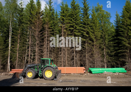 Tractor and drainage pipes at road building site , Finland