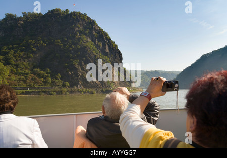 Tourists on a tourist ship driving on the river Rhine at the Loreley rock in the German Middle-Rhein Valley - Stock Photo
