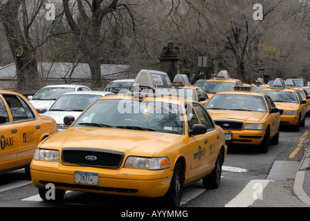 Taxicabs and other vehicles leave a Central Park transverse and cross Fifth Avenue - Stock Photo