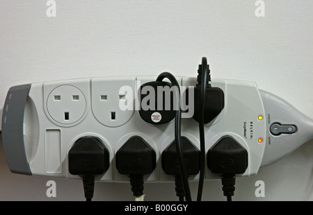 Surge protector with six electrical plugs connected - Stock Photo
