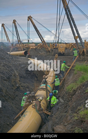 Specialist contractors weld section of large diameter high-pressure  natural gas steel pipeline suspended from sideboom - Stock Photo