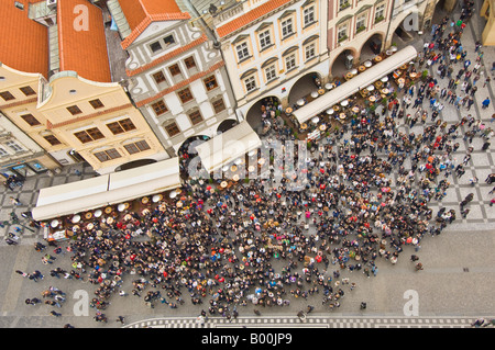 Crowds gather to watch the famous hourly show of Apostle figures on the medieval astronomical clock in the Old Town - Stock Photo