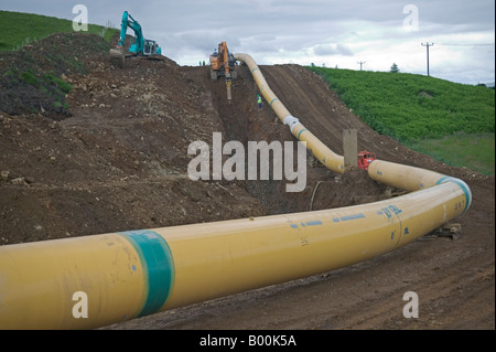 A large diameter gas transmission steel pipeline must be shaped carefully to fit the contours of the undulating - Stock Photo