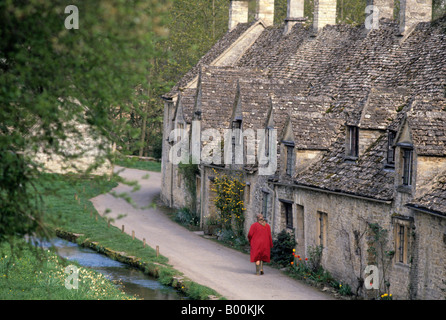 A lady in red coat walks past Cotswold cottages, Bibury, Gloucestershire, England - Stock Photo