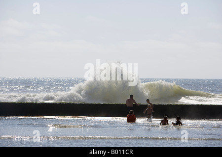 Namibia, Erongo Region, Swakopmund. A tidal pool on the outskirts of Swakopmund where the waves crash onto the outside - Stock Photo