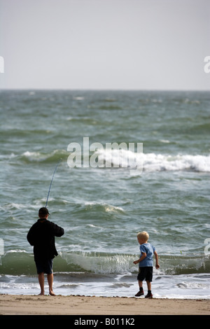 Namibia, Erongo Region, Swakopmund. Just outside of Swakopmund, two young boys fish on the Skeleton Coast. - Stock Photo