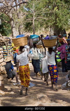 Mali, Dogon Country. Dogon women carry their farm produce to the small but popular weekly market at Tereli. - Stock Photo