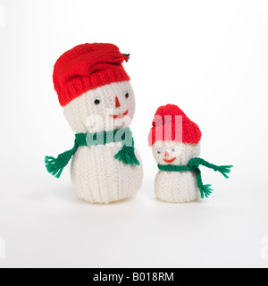 2 knit snowmen with red caps and green scarves - Stock Photo