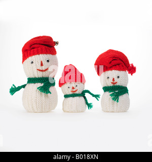 3 knit snowmen family with red caps and green scarves - Stock Photo