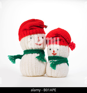 snowmen figurines knitted wearing green scarves and red caps on white background - Stock Photo