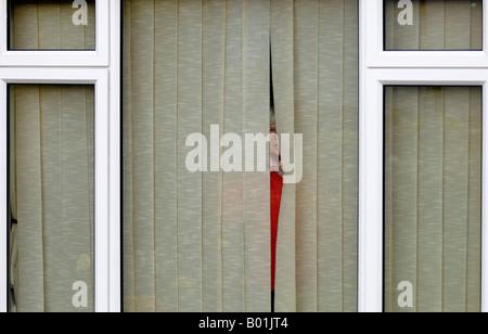 woman watching street through curtains - Stock Photo