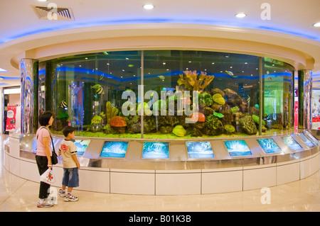 Circular aquarium in Interior of shopping mall in Singapore - Stock Photo