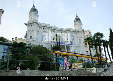 2 children wearing French berets, sitting on railing, Admiral Casino building in background. Opatija, Croatia - Stock Photo