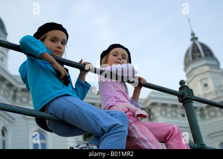 2 children wearing French berets, sitting on railing, Admiral Casino building (out of focus) in background. Opatija, - Stock Photo