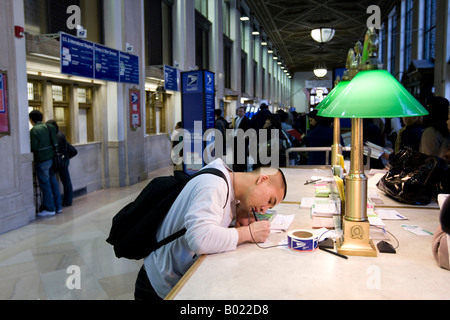 A man prepares an envelope to mail in the lobby of the Farley Post Office in New York 15 April 2008 - Stock Photo