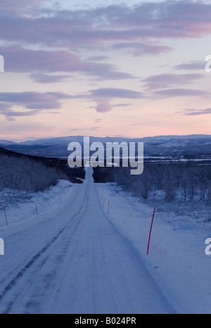 Icy road at Kilpisjärvi, Finnish Lappland, in fading pink mid-winter light at noon - Stock Photo