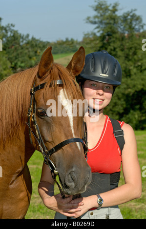 Young rider wearing a riding helmet and a spine protector with Arabian horse - Stock Photo