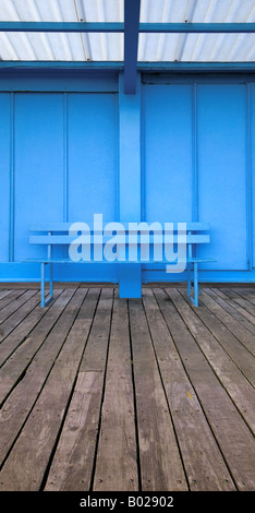 Vertical panoramic image of an empty blue bench on wooden decking - Stock Photo