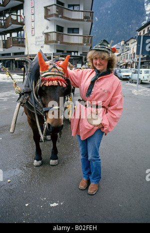 A young woman with her horse drawn wagon in downtown Chamonix France a popular ski resort in the Alps - Stock Photo