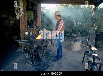 Blacksmith Mark Simmons heats iron implements in his blacksmith shop near Santa Fe New Mexico - Stock Photo