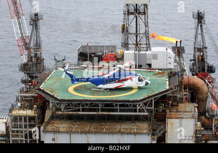 A Bristows S-92 helicopter on the helideck of an oil rig in the North Sea off the coast of North East Scotland - Stock Photo