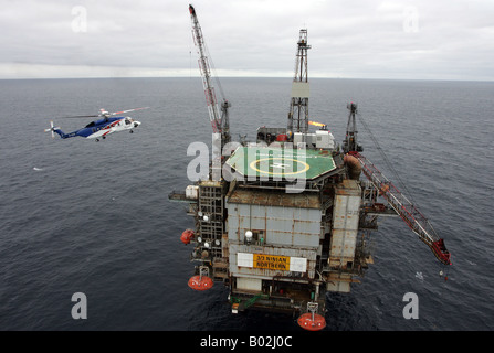 A Bristows S-92 helicopter lands on an oil rig in the North Sea off the coast of North East Scotland - Stock Photo