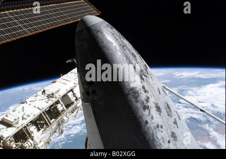 Space Shuttle Discovery docked to the International Space Station. - Stock Photo