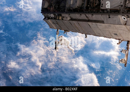 Astronaut participates in a session of extravehicular activity (EVA) as construction resumes on the International - Stock Photo