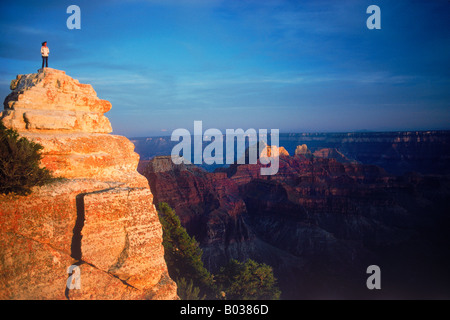 Visitor standing on Bright Angel Point along North Rim of Grand Canyon in sunset light - Stock Photo