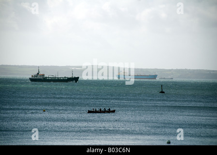Silhouette of Gig boat racers with large cargo ships in background, St Mawes, Cornwall - Stock Photo
