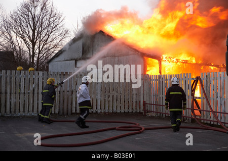 FIRE SERVICE ATTACKING BURNING BUILDING - Stock Photo