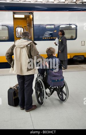 Wheelchair passenger waits to board a Eurostar train at Kings Cross / Saint Pancras International station. London. - Stock Photo