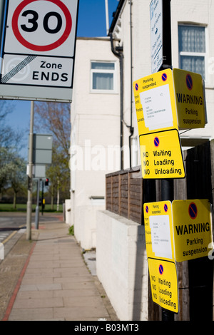 large number of warning and parking signs on a post in a street - Stock Photo