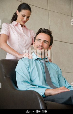 Woman giving massage to colleague - Stock Photo