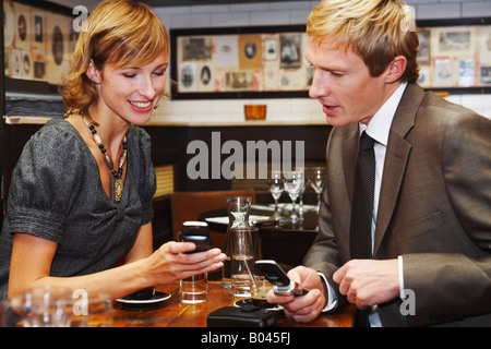 Couple with Cell Phones in Cafe - Stock Photo