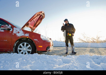 Man Talking on Cell Phone Next to Car with Hood Up in Winter - Stock Photo